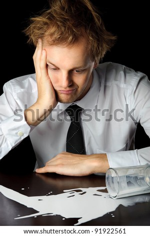 Caucasian man in business attire is upset about his spilled milk, isolated on black