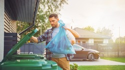 Caucasian Man is Throwing Away Two Plastic Bags of Trash next to His House. One Garbage Bag is Sorted with Biological Food Waste, Other with Recyclable Bottles Garbage Bin.