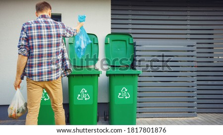 Caucasian Man is Throwing Away Two Plastic Bags of Trash next to His House. One Garbage Bag is Sorted with Biological Food Waste, Other with Recyclable Bottles Garbage Bin. Stockfoto ©