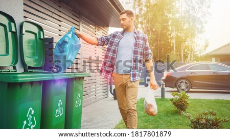 Caucasian Man is Throwing Away Two Plastic Bags of Trash next to His House. One Garbage Bag is Sorted with Biological Food Waste, Other with Recyclable Bottles Garbage Bin. Foto stock ©