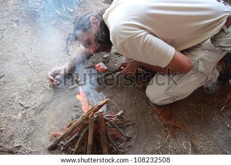 caucasian man lighting a fire camp