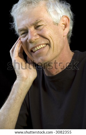 Caucasian man of sixty, gray hair, hand to face, with a big laugh, dark background