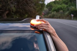 Caucasian man placing the new Emergency Light for damaged vehicles (V16 luminous beacon), which must be replaced by triangles. road safety.