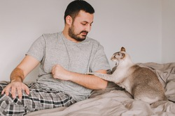 Caucasian man playing with cat. Angry furious cat attacking scratching owner master. Guy lying on bed at home with oriental cat. Pet owner with aggressive domestic animal.