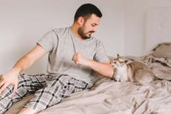 Caucasian man playing with cat. Angry furious cat biting scratching owner master hand. Guy lying on bed at home with oriental cat. Pet owner with domestic animal.