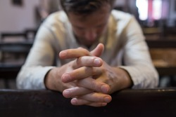 caucasian man praying in church. He has problems and ask God for help. Concept of religion faith