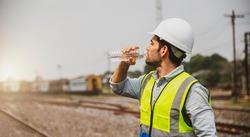 Caucasian man railway engineer drink water from bottle in the site work of train garage.