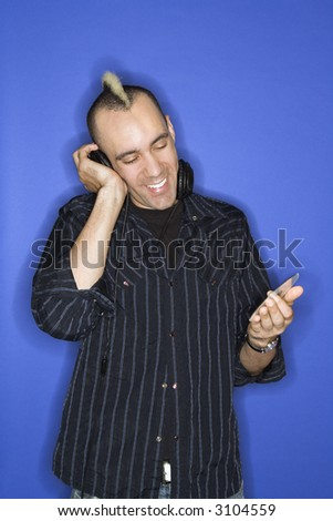 Caucasian man smiling with mohawk listening to headphones holding cd standing against blue background.