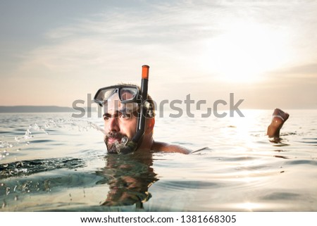 Caucasian man snorkelling,floating on the surface,spitting out water with a funny goofy facial expression,summer seaside vacation activity,cancelled due to Coronavirus COVID-19 global pandemic crisis Foto stock ©