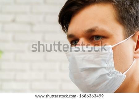 Caucasian man staying at home during Coronavirus / Covid-19 quarantine wearing medical mask