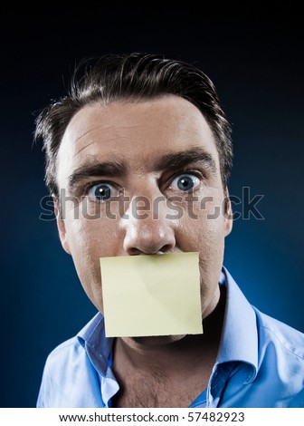 caucasian man surprised mouth shut by note paper portrait isolated studio on black background