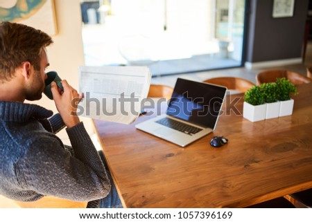 Caucasian man taking a sip of his morning cup of coffee while reading newspaper at his beautiful dining table, with his notebook in front of him for when he is ready to get to work.