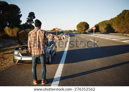 Caucasian man trying stop cars in travel because his car broken down. Young man stand on freeway and shows thumbs up. Young interracial man in their twenties.