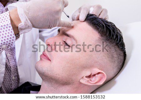 Photo of  Caucasian man undergoing beauty spa botulinum neurotoxin Botox treatment for anti-aging, to smooth wrinkles as a cometic solution. Injecting forehead to relax muscles with a non-invasive procedure.