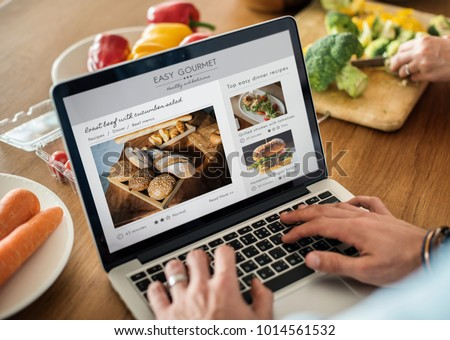 Caucasian man using a laptop in the kitchen searching for recipes