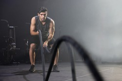Caucasian Man Using Battle Ropes For Whipping Exercise  in a Gym