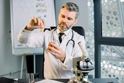 Caucasian man virologist, bio chemist, scientist wearing white coat holding test tube and dropped red liquid to flask. Chemist examines chemical test tube, sitting at the table in modern lab