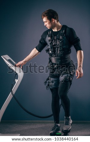 Caucasian man wearing biometric fitness vest training on stepper with electric muscle stimulation #1038440164