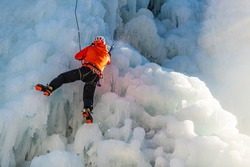 Caucasian man with climbing equipment hiking at a frozen waterfall