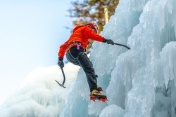 Caucasian man with climbing equipment, ice axes and rope, hiking at a frozen waterfall