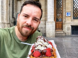 Caucasian man with dark hair, dark eyes, and a dark beard holding a bright colorful Belgian waffle in Brussels, Belgium. Pastry with berries, chocolate, and whipped cream. Tourist activity on vacation