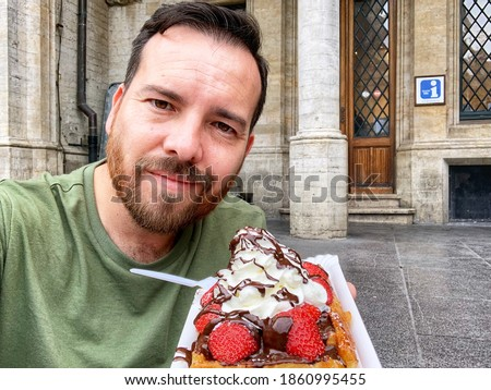 Caucasian man with dark hair, dark eyes, and a dark beard holding a bright colorful Belgian waffle in Brussels, Belgium. Pastry with berries, chocolate, and whipped cream. Tourist activity on vacation Foto stock ©