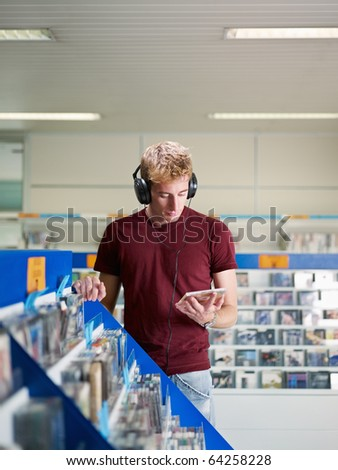 caucasian man with headphones, choosing cd in music shop. Vertical shape, front view, waist up, copy space