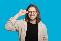 Caucasian man with long hair and beard looking through eyeglasses is smiling cheerfully on a blue wall