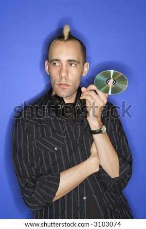 Caucasian man with mohawk with headphones holding cd standing against blue background.