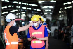 Caucasian Managers checking fever of foreman with an infrared thermometer and putting sanitizer gel on hand at factory. As  precautionary measure and surveillance of coronavirus or covid-19 outbreak