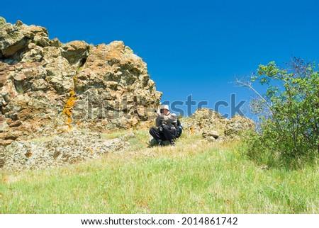 Caucasian mature photographer is taking photos on Kara-dag (extinct volcan) natural reserve, Eastern Crimea Stockfoto ©