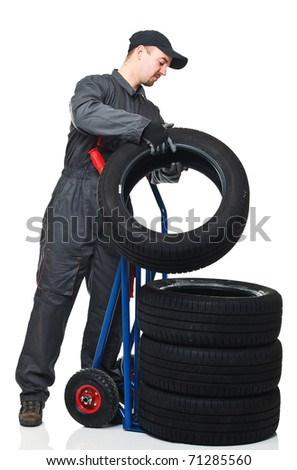 caucasian mechanic pose tire on handtruc isolated on white background