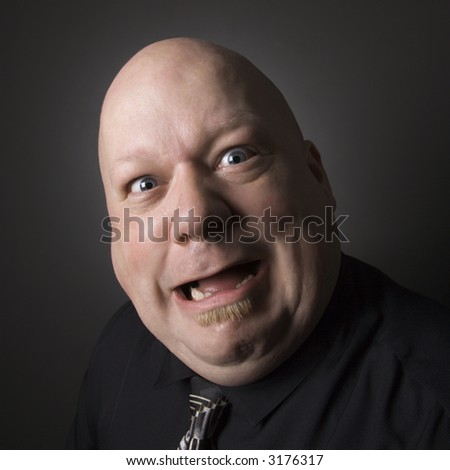 Caucasian mid adult bald man looking at viewer and making facial expression.