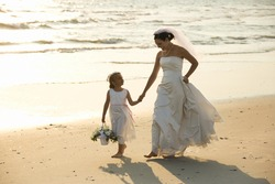 Caucasian mid-adult bride and flower girl holding hands walking barefoot on beach.