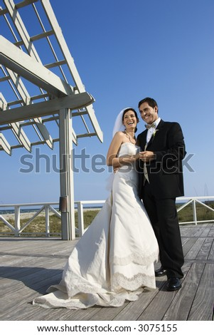Caucasian mid-adult bride and groom wedding portrait outside at beach.