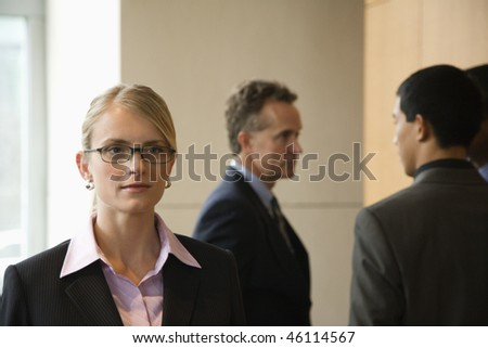 Caucasian mid-adult business woman in foreground with group of businessmen in the background. Horizontal format.