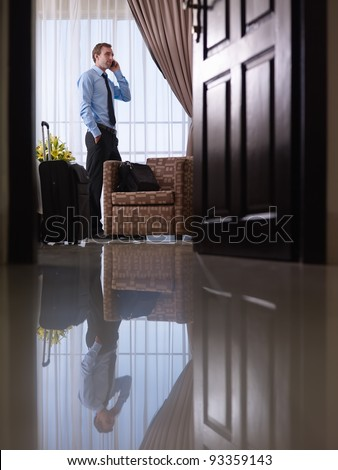 Caucasian mid adult businessman talking with mobile telephone in hotel room during business trip