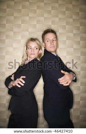 Caucasian mid-adult businesswoman and middle-aged businessman standing back to back and peering at each other over their shoulders. Vertical format.