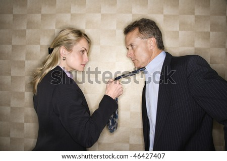Caucasian mid-adult businesswoman staring into eyes of a middle-aged businessman while pulling on his tie. Horizontal format.