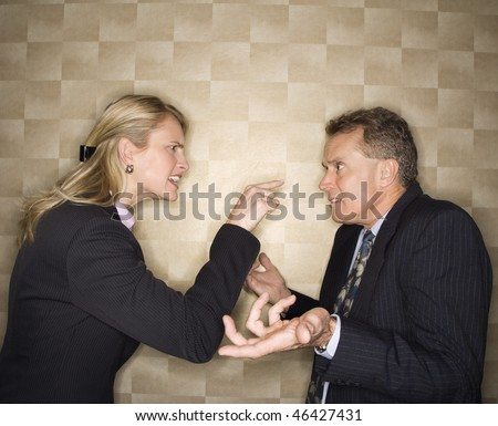 Caucasian mid-adult businesswoman yelling and pointing at middle-aged businessman, who shrugs at her. Horizontal format.