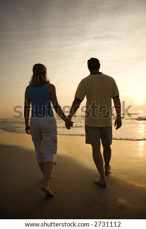 Caucasian mid-adult couple walking holding hands on beach at sunset.