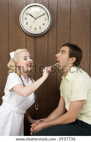 Caucasian mid-adult female nurse  examinating male's mouth with tongue depressor.