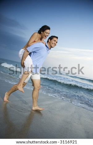 stock photo : Caucasian mid-adult male carrying female piggyback style on ...