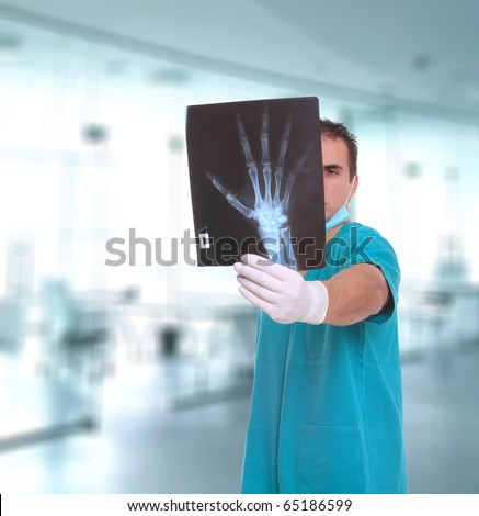 Caucasian mid adult male doctor with xray posing over light medical environment background