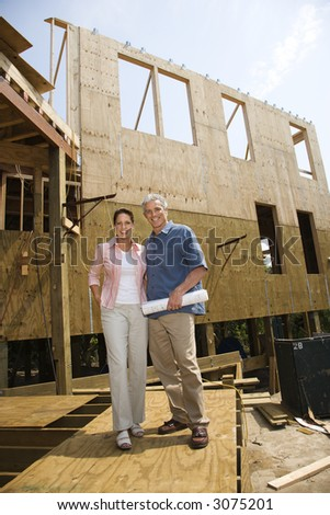 Caucasian mid-adult male holding blue prints with arm around mid-adult female in building construction site.