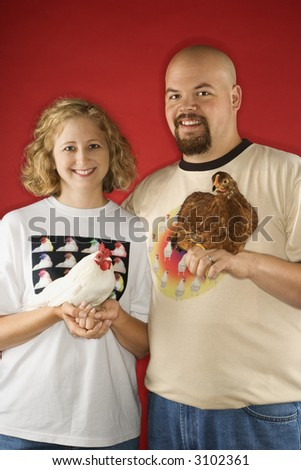 Caucasian mid-adult man and woman holding chickens. - stock photo