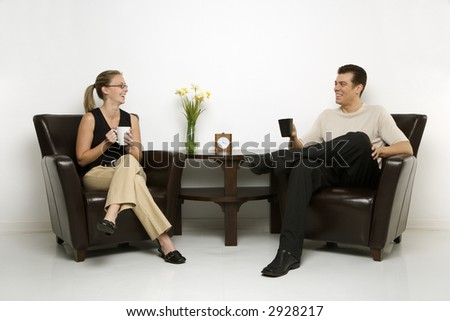 Caucasian mid-adult man and woman sitting in armchairs drinking coffee.
