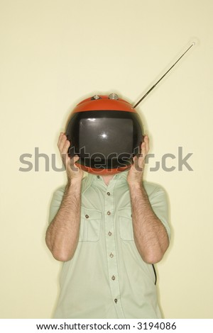 Caucasian mid-adult man holding round red retro television in place of head.