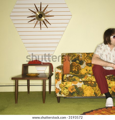 Caucasian mid-adult man sitting on colorful retro sofa wearing sunglasses in room with vintage decor.