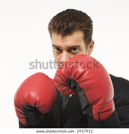 Caucasian mid-adult man wearing suit and holding boxing gloves close to his face.